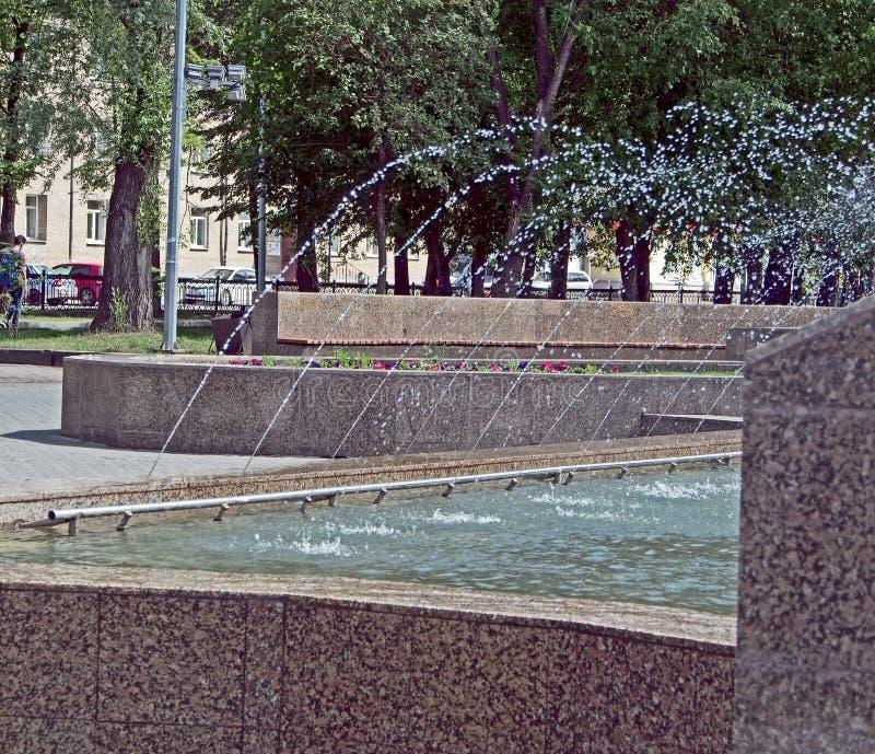 Η λειτουργώντας πηγή στο τετράγωνο πόλεων μια καυτή ημέρα, πετώντας νερό μειώνεται στοκ εικόνες με δικαίωμα ελεύθερης χρήσης
