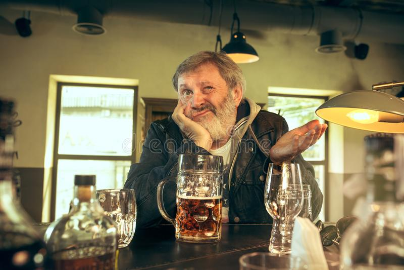 Η λυπημένη ανώτερη γενειοφόρος αρσενική μπύρα κατανάλωσης στο μπαρ στοκ φωτογραφία με δικαίωμα ελεύθερης χρήσης