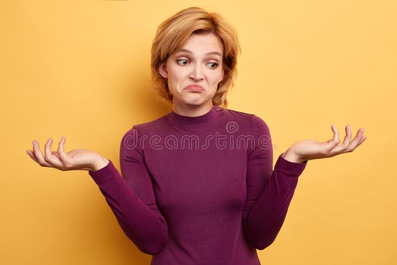 Η λυπημένη δυστυχισμένη γυναίκα με τα αυξημένα χέρια δεν μπορεί να βρεί τη λύση του προβλήματος στοκ εικόνα με δικαίωμα ελεύθερης χρήσης