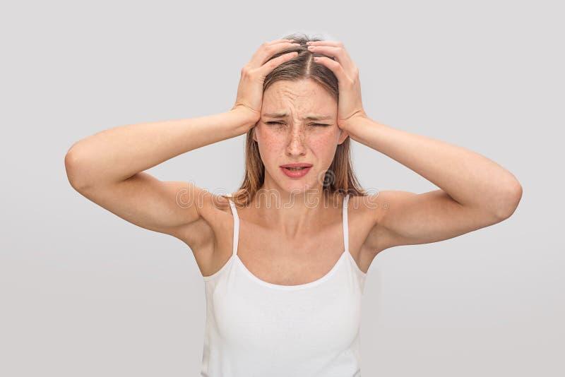 Η λυπημένη και νέα γυναίκα στέκεται και κοιτάζει στη κάμερα Κρατά τα χέρια στο κεφάλι Το πρότυπο έχει τον πονοκέφαλο Υποφέρει Νέο στοκ εικόνες με δικαίωμα ελεύθερης χρήσης