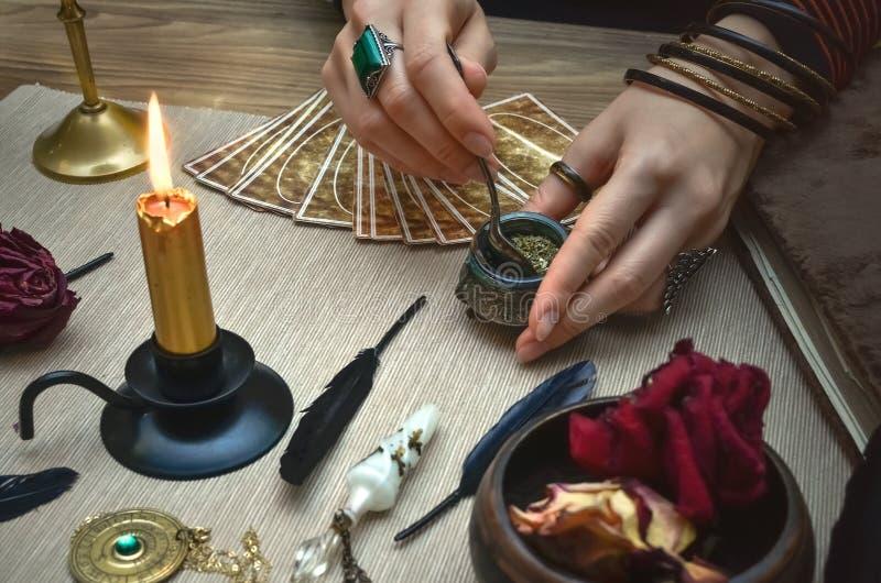 Η μάγισσα γυναικών προετοιμάζει μια μαγική φίλτρο κάρτες tarot Μελλοντική ανάγνωση Έννοια αφηγητών τύχης στοκ φωτογραφία