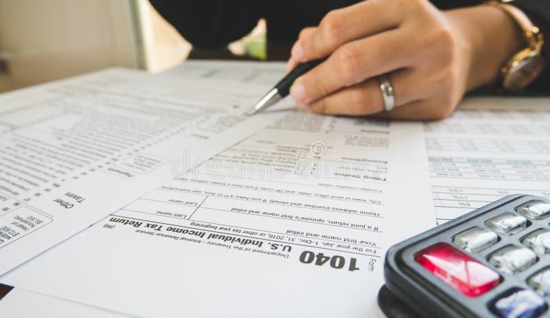 Η μάνδρα λαβής χεριών επιχειρησιακών γυναικών συμπληρώνει τις λεπτομέρειες σε χαρτί φορολογικών μορφών στην επιχειρησιακή έννοια στοκ φωτογραφία