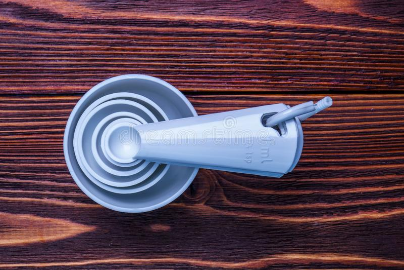 Η μέτρηση του καθορισμένου πίνακα μετακινεί με το κουτάλι και πλαστικό άσπρο χρώμα φλυτζανιών στο woode στοκ φωτογραφία με δικαίωμα ελεύθερης χρήσης