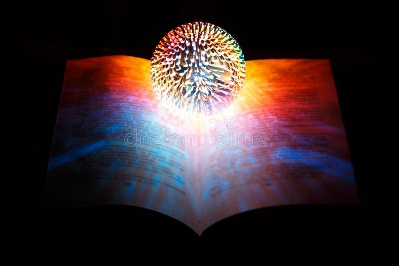Η μαγική σφαίρα fortuneteller, η μάγισσα, βρίσκεται στο ανοιγμένο μαγικό βιβλίο σε ένα μαύρο υπόβαθρο απεικόνιση αποθεμάτων