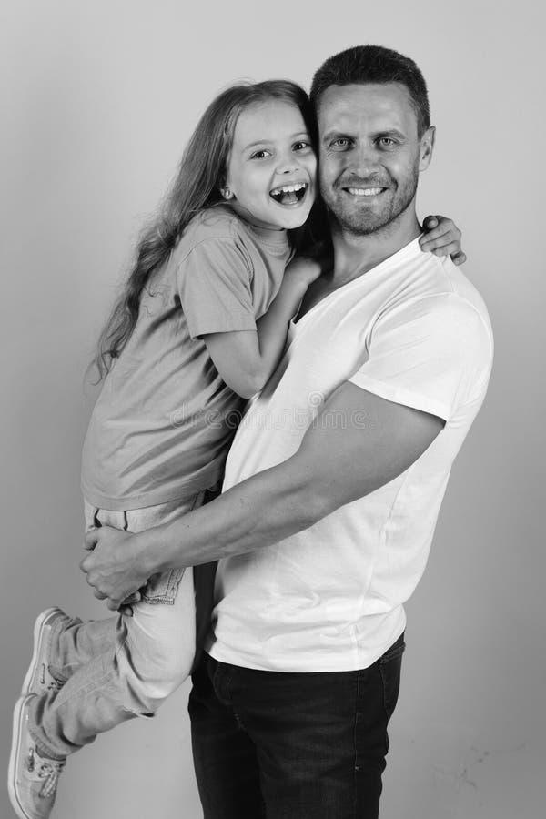 Η μαθήτρια κάθεται στα όπλα dads Η κόρη και ο πατέρας αγκαλιάζουν η μια την άλλη Παιδική ηλικία και οικογενειακή έννοια στοκ εικόνα με δικαίωμα ελεύθερης χρήσης