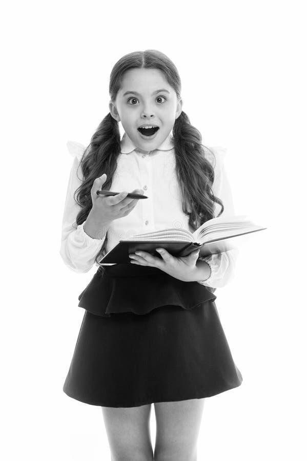 Η μαθήτρια με έκπληκτος φαίνεται απομονωμένη στο λευκό Λίγο βιβλίο λαβής παιδιών με τη μάνδρα πίσω σχολείο Εγχώρια εκπαίδευση στοκ εικόνα