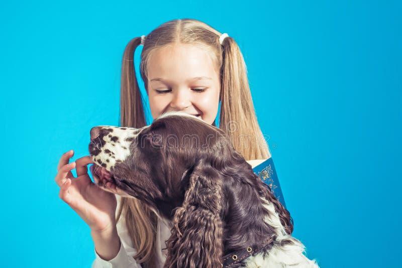 Η μαθήτρια παιδιών παίρνει ένα βιβλίο και παίζει με το σκυλί της στο μπλε σχολικό κορίτσι backgroundild που διαβάζει ένα βιβλίο σ στοκ φωτογραφίες με δικαίωμα ελεύθερης χρήσης