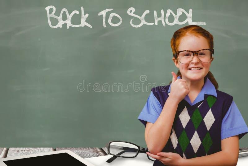 Η μαθήτρια που παρουσιάζει αντίχειρα υπογράφει επάνω ενώ πίσω στο σχολείο γράφεται στον πίνακα κιμωλίας στοκ εικόνες