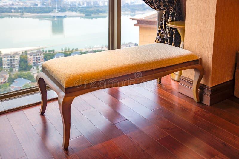 Η μακριά καρέκλα σαλονιών κοντά στο παράθυρο νέο εσωτερικό, μέσω του παραθύρου μια νέα κεντρική περιοχή βιλών από τον ποταμό μπορ στοκ φωτογραφία με δικαίωμα ελεύθερης χρήσης