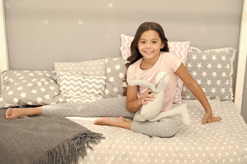 Η μακριά σγουρή τρίχα κοριτσιών απολαμβάνει το χρόνο με το αγαπημένο παιχνίδι Το παιδί κάθεται το κρεβάτι και παίζει το σύγχρονο  στοκ εικόνα με δικαίωμα ελεύθερης χρήσης