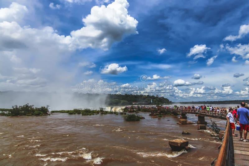 Η μακριά σειρά αναμονής των τουριστών στη διάβαση πεζών μετάλλων προς την κορυφή του λαιμού διαβόλων σε Iquazu πέφτει στοκ εικόνες