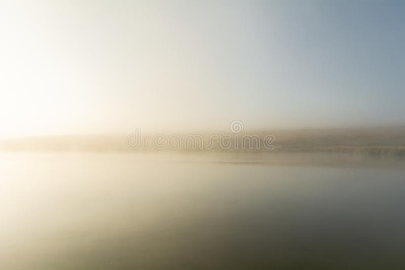 Η μακρινή ακτή της λίμνης είναι μόλις ορατή λόγω της ισχυρής ομίχλης πρωινού στην αυγή Ύφος μινιμαλισμού στοκ φωτογραφίες με δικαίωμα ελεύθερης χρήσης