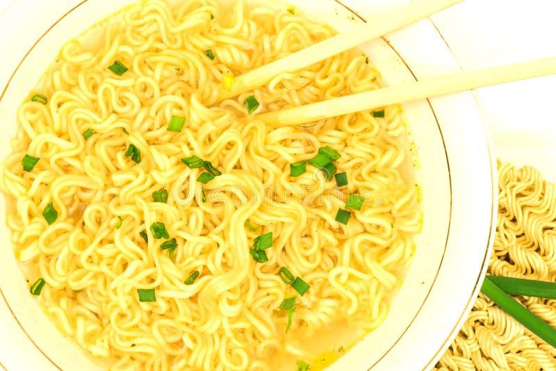 Η μακρο άποψη του πιάτου της σούπας γρήγορου γεύματος με το πράσινο κρεμμύδι, chopsticks και ακατέργαστος το στιγμιαίο νουντλς άψ στοκ φωτογραφία με δικαίωμα ελεύθερης χρήσης