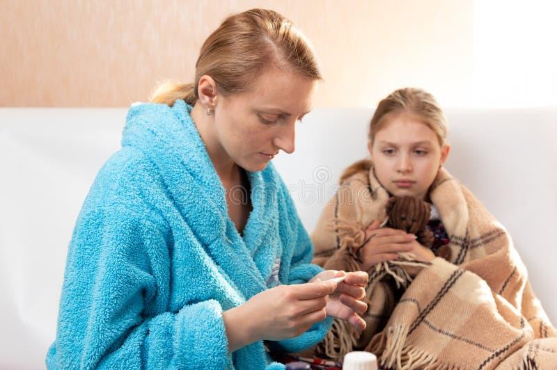 Η μαμά μετρά τη θερμοκρασία ενός παιδιού Το παιδί αρρώστησε στοκ εικόνες