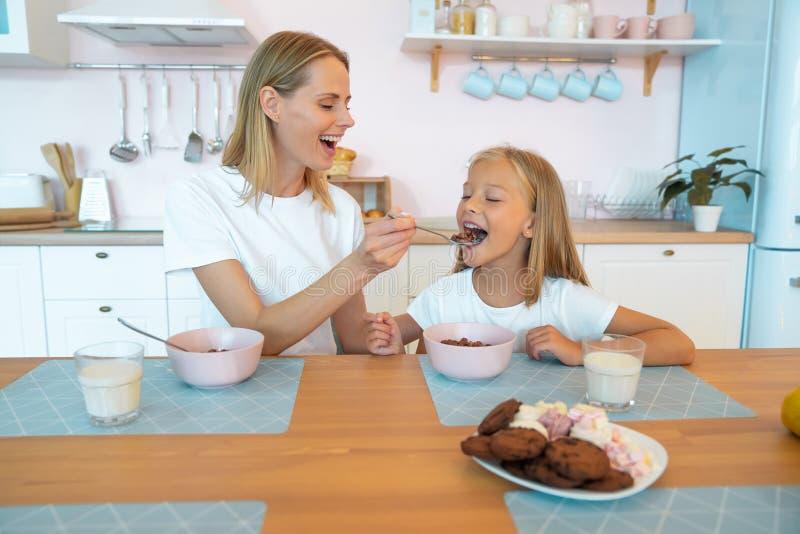 Η μαμά τρέφει την όμορφη κόρη της με σοκολατένιες νιφάδες διασκεδάστε μαζί, ντυμένοι στοκ εικόνες με δικαίωμα ελεύθερης χρήσης