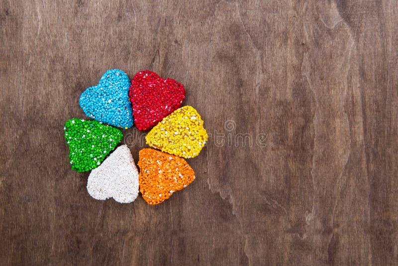 Η μαρμελάδα είναι ένα χρωματισμένο ζάχαρη ουράνιο τόξο Μαρμελάδα υπό μορφή καρδιάς Γλυκά σε ένα ξύλινο υπόβαθρο Τριφύλλι γλυκών μ στοκ φωτογραφία με δικαίωμα ελεύθερης χρήσης