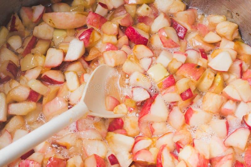 Η μαρμελάδα μήλων μαγείρων και ανακατώνει με ένα άσπρο πλαστικό κουτάλι Διαδικασία του μ στοκ εικόνα με δικαίωμα ελεύθερης χρήσης