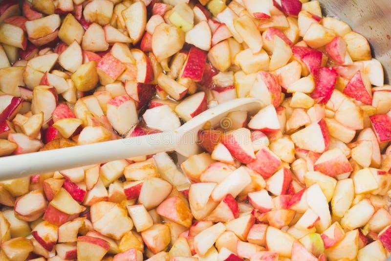 Η μαρμελάδα μήλων μαγείρων και ανακατώνει με ένα άσπρο πλαστικό κουτάλι Διαδικασία του μ στοκ φωτογραφία με δικαίωμα ελεύθερης χρήσης