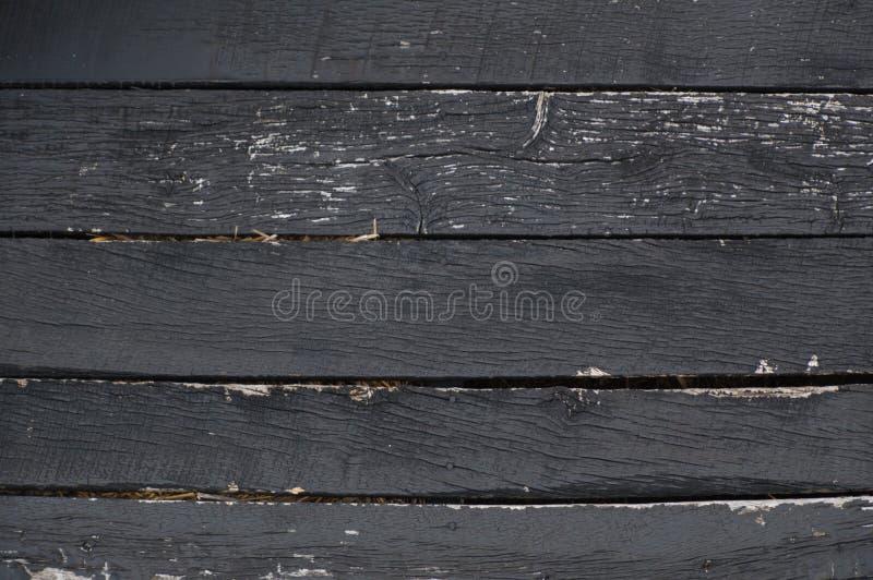 Η μαύρη αποφλοίωση ξεπέρασε τους οριζόντιους ξύλινους πίνακες με το άχυρο στοκ εικόνες
