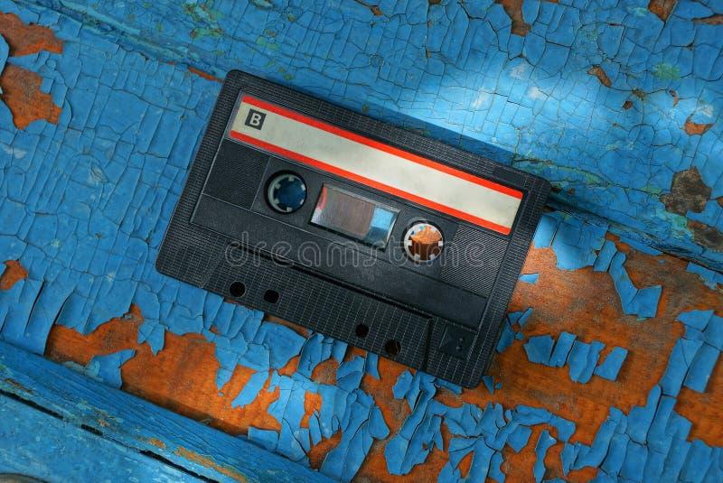η μαύρη παλαιά ακουστική κασέτα βρίσκεται σε έναν μπλε γρατζουνισμένο πίνακα στοκ φωτογραφία με δικαίωμα ελεύθερης χρήσης