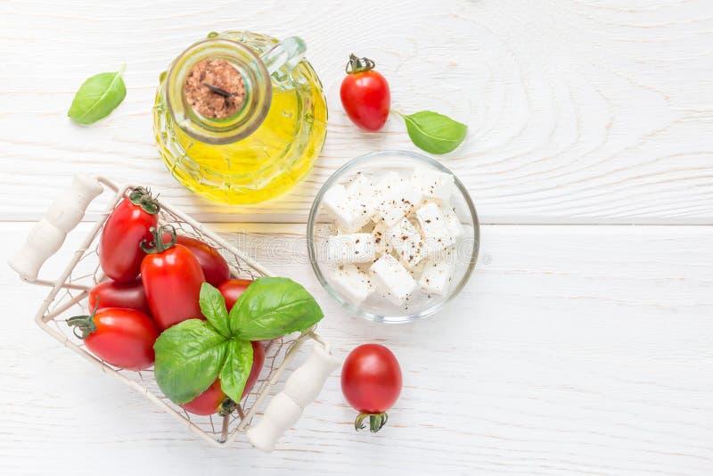 η μαύρη σαλάτα ελιών μαρουλιού συστατικών σπάζει απότομα την ντομάτα ζάχαρης Ντομάτες κερασιών, βασιλικός, τυρί φέτας και ελαιόλα στοκ εικόνα