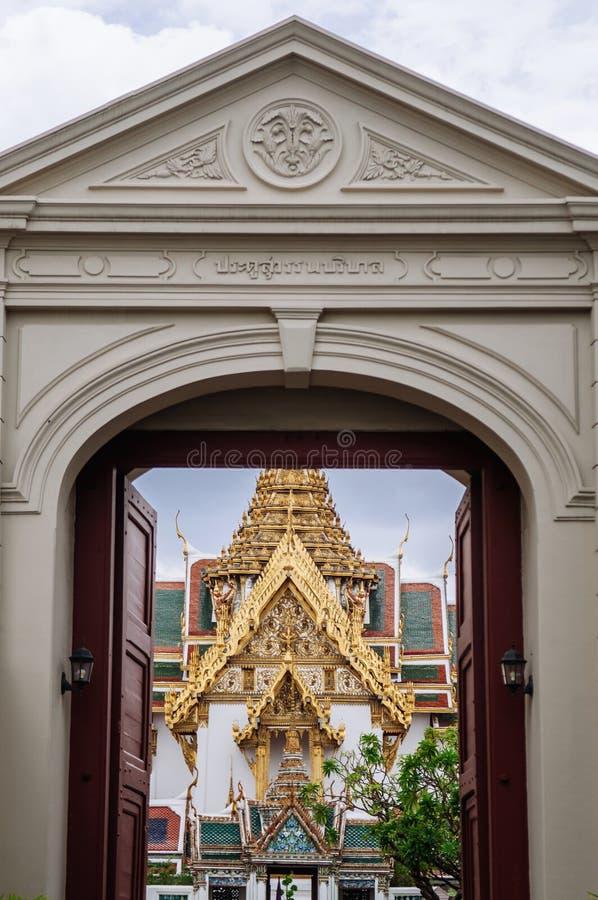 Η μεγάλη αίθουσα θρόνων παλατιών ` Dusit Maha Prasat ` της Μπανγκόκ που βλέπει μέσω maingate και του αλφάβητου πάνω από την πύλη  στοκ εικόνες με δικαίωμα ελεύθερης χρήσης