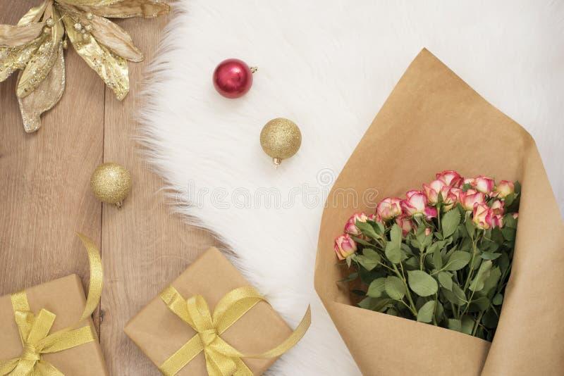 Η μεγάλη ανθοδέσμη πολυτέλειας των τριαντάφυλλων, οι σφαίρες Χριστουγέννων και τα δώρα σε μια γούνα καλύπτουν με τάπητα Έννοια χε στοκ φωτογραφία με δικαίωμα ελεύθερης χρήσης