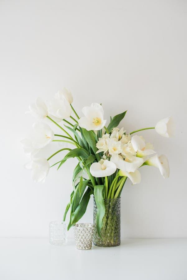 Η μεγάλη ανθοδέσμη του άσπρου ελατηρίου ανθίζει σε ένα βάζο, daffodils, tuli στοκ εικόνες