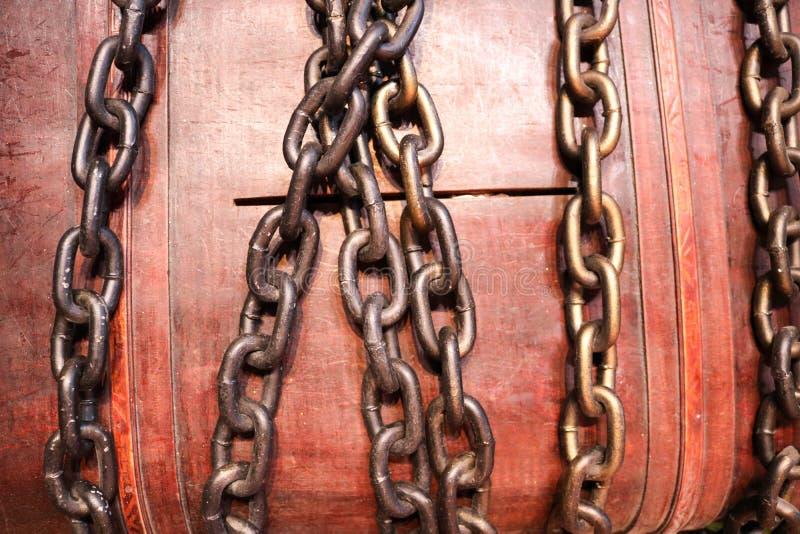 Η μεγάλη, καφετιά, ξύλινη κασετίνα, μια piggy τράπεζα, ένα στήθος δέσμευσε, κλειστός με τις ισχυρές αλυσίδες σιδήρου στοκ φωτογραφία με δικαίωμα ελεύθερης χρήσης