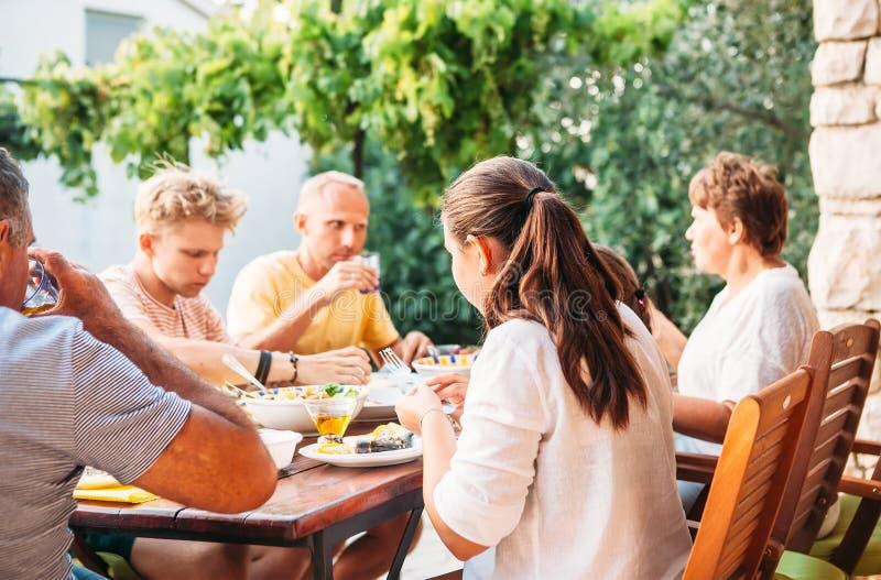 Η μεγάλη οικογένεια έχει το γεύμα στο ανοικτό πεζούλι κήπων στοκ φωτογραφία με δικαίωμα ελεύθερης χρήσης
