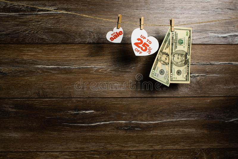 Η μεγάλη πώληση σε 25 τοις εκατό που γράφονται στην άσπρη καρδιά και κρεμά στη σκοινί για άπλωμα με δύο τραπεζογραμμάτια των δολα στοκ εικόνα με δικαίωμα ελεύθερης χρήσης
