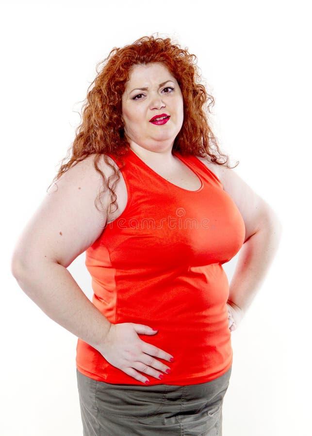 Η μεγάλη γυναίκα με το κόκκινο κραγιόν και το μεγάλο κοιλιακό πόνο, κακή διάθεση στοκ εικόνες