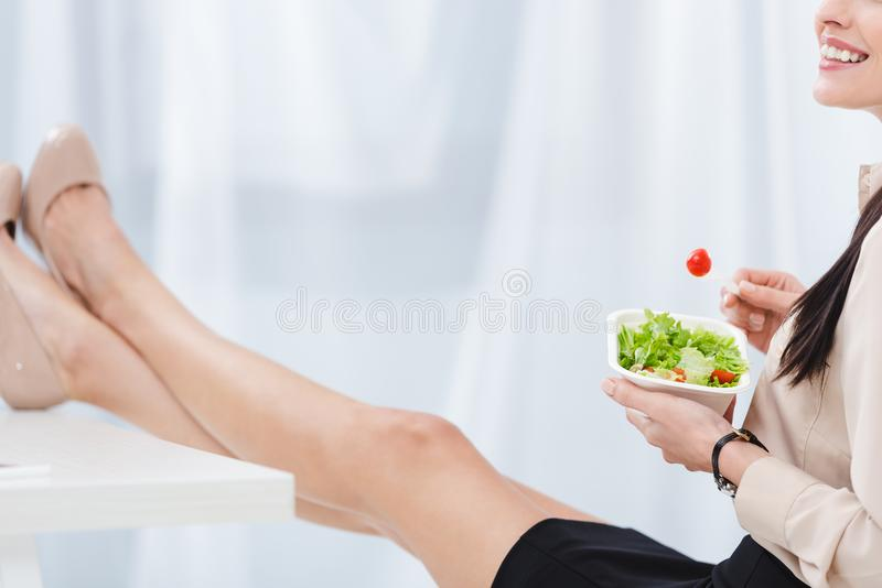 η μερική άποψη της επιχειρηματία με παίρνει μαζί τα τρόφιμα στον εργασιακό χώρο στοκ εικόνες