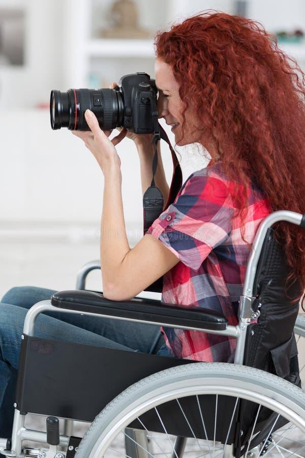 Η με ειδικές ανάγκες γυναίκα στην αναπηρική καρέκλα έχει το πάθος για τη φωτογραφία στοκ εικόνα