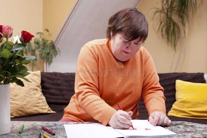 Η με ειδικές ανάγκες γυναίκα χρωμάτισε με τα μολύβια σε ένα βιβλίο στοκ φωτογραφία
