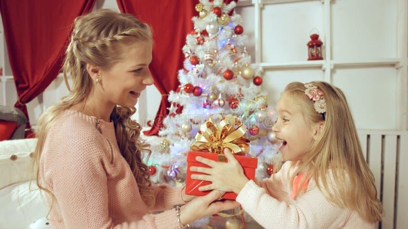 Η μητέρα δίνει ένα νέο δώρο έτους στην κόρη της στοκ εικόνες