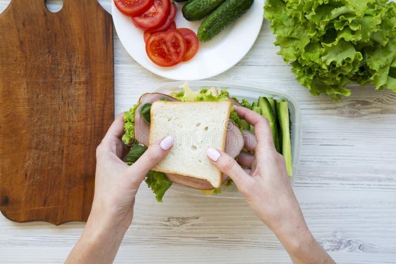 η μητέρα βάζει τα σάντουιτς στο καλαθάκι με φαγητό Τοπ όψη στοκ εικόνες