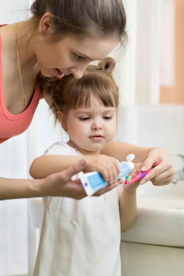 Η μητέρα βάζει την οδοντόπαστα σε μια βούρτσα παιδιών, βουρτσίζοντας τα δόντια στοκ εικόνες