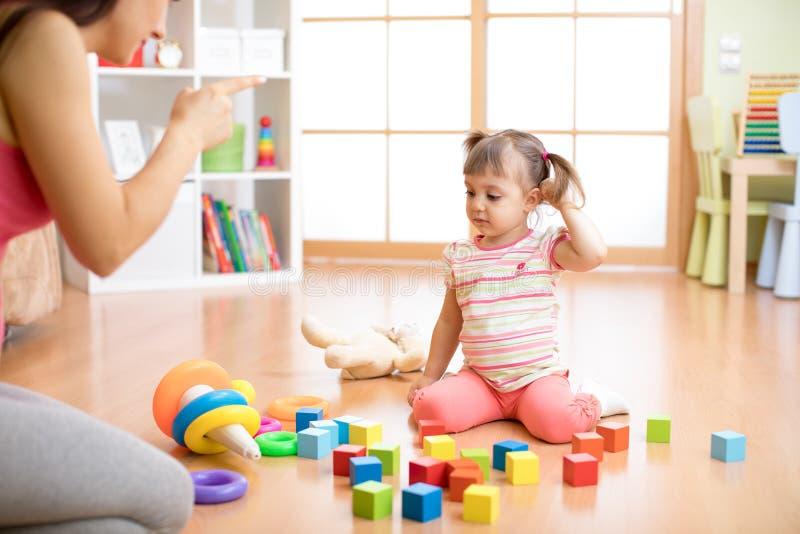 Η μητέρα βλέπει στα παιχνίδια παιχνιδιού κορών της ακατάστατα επάνω το καθιστικό αισθάνεταιη και επικρίνει το κορίτσι παιδιών θλί στοκ εικόνες