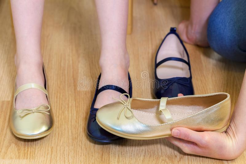 Η μητέρα βοηθά μια κόρη να προσπαθήσει στα παπούτσια στοκ εικόνες