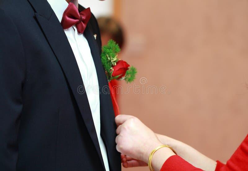 Η μητέρα βοηθά το γιο της που είναι ο νεόνυμφος για να φορέσει το γαμήλιο κορσάζ του στο κοστούμι νεόνυμφων ` s στοκ εικόνες με δικαίωμα ελεύθερης χρήσης