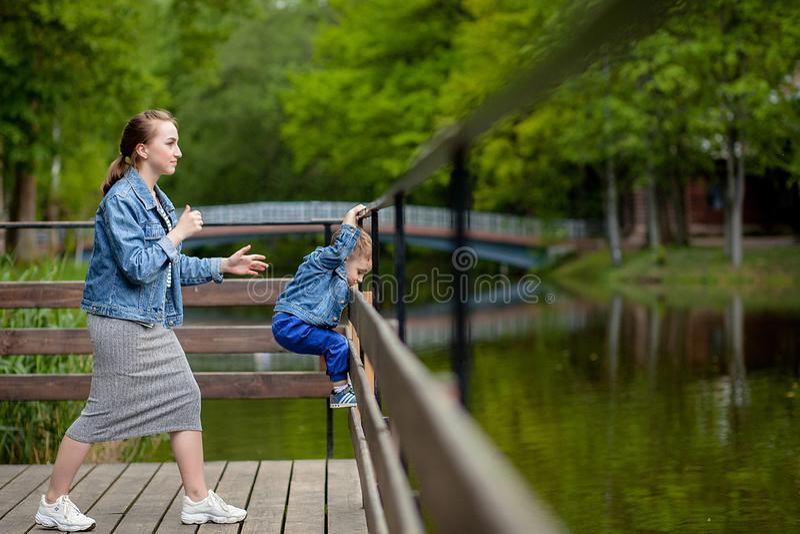 Η μητέρα δοκιμάζει ότι το παιδί θα περιέλθει στο νερό Ένα μικρό αγόρι αναρριχείται σε ένα κιγκλίδωμα γεφυρών στο πάρκο Η απειλή στοκ εικόνες