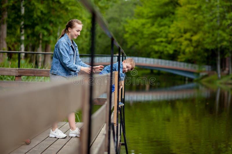 Η μητέρα δοκιμάζει ότι το παιδί θα περιέλθει στο νερό Ένα μικρό αγόρι αναρριχείται σε ένα κιγκλίδωμα γεφυρών στο πάρκο Η απειλή στοκ φωτογραφία με δικαίωμα ελεύθερης χρήσης