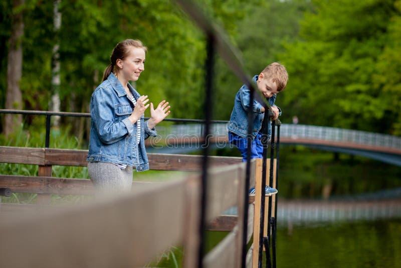 Η μητέρα δοκιμάζει ότι το παιδί θα περιέλθει στο νερό Ένα μικρό αγόρι αναρριχείται σε ένα κιγκλίδωμα γεφυρών στο πάρκο Η απειλή στοκ φωτογραφία