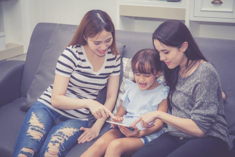Η μητέρα, η θεία και το παιδί που έχουν το χρόνο που μαζί με τη χρησιμοποίηση της ταμπλέτας στο σπίτι με χαλαρώνουν και ευτυχής σ στοκ φωτογραφία