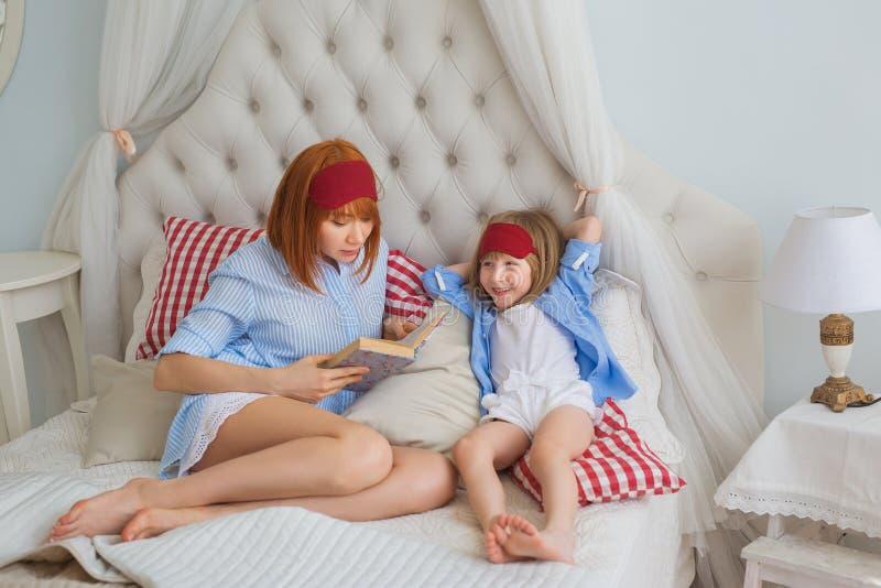 Η μητέρα διαβάζει ένα βιβλίο σε λίγη κόρη σε ένα κρεβάτι στοκ φωτογραφία με δικαίωμα ελεύθερης χρήσης