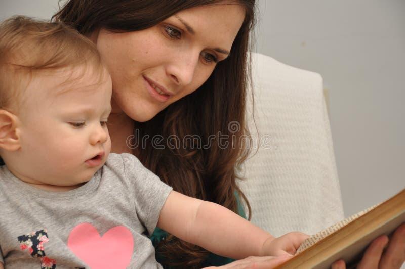 Η μητέρα διαβάζει ένα βιβλίο σε μια κόρη μωρών στοκ φωτογραφίες