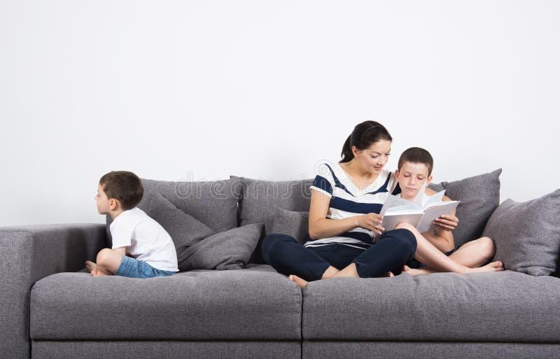 Η μητέρα διαβάζει ένα ενδιαφέρον βιβλίο με τους γιους της Έννοια ζηλοτυπίας στοκ φωτογραφία με δικαίωμα ελεύθερης χρήσης