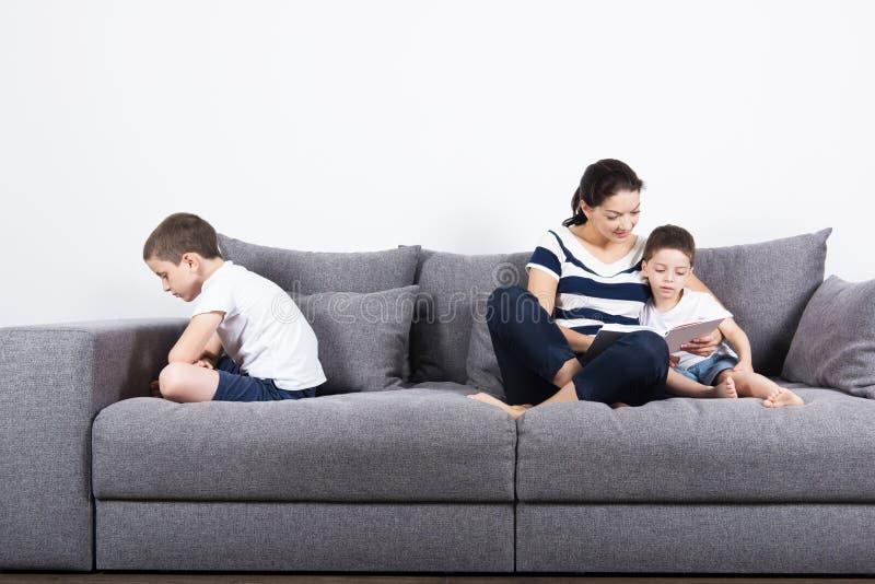 Η μητέρα διαβάζει ένα ενδιαφέρον βιβλίο με τους γιους της Έννοια ζηλοτυπίας στοκ εικόνες
