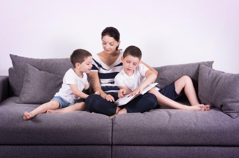 Η μητέρα διαβάζει ένα ενδιαφέρον βιβλίο με τους γιους της του καναπέ στοκ φωτογραφία